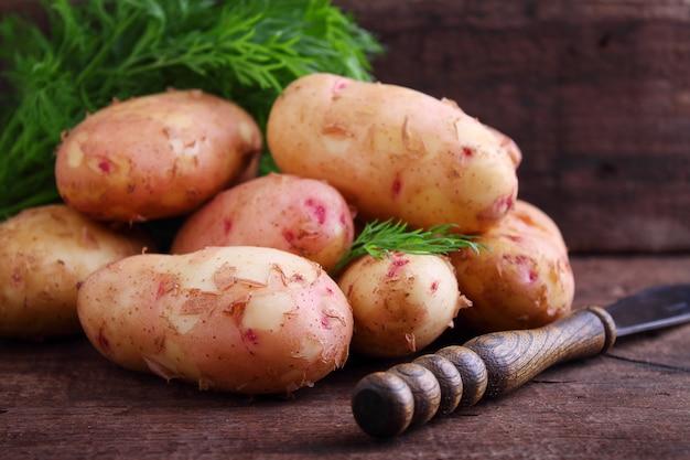 나무 배경에 나무 접시에 젊은 감자