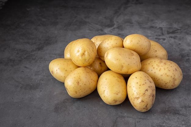 暗いテーブルで若いジャガイモ。作物。収穫