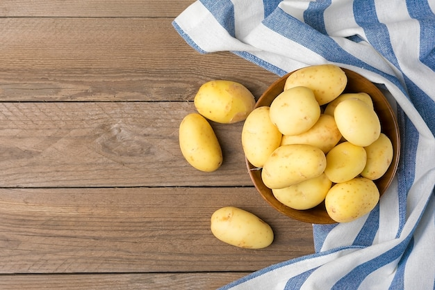 Young potatoes in a wooden bowl, napkin with blue and white stripes on wooden table. rustic style. top view. flat lay.