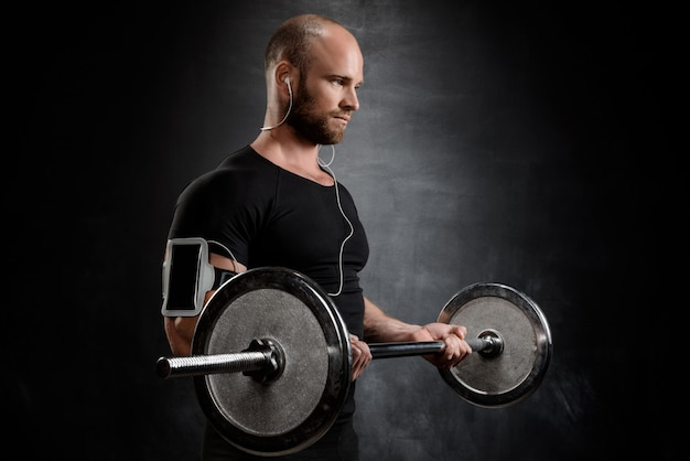 Young powerful sportsman training with barbell over black wall.