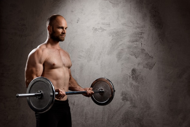 Young powerful sportsman training with barbell over dark wall.