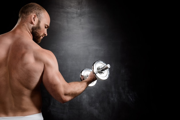 Young powerful sportsman training with dumbbells over black wall.