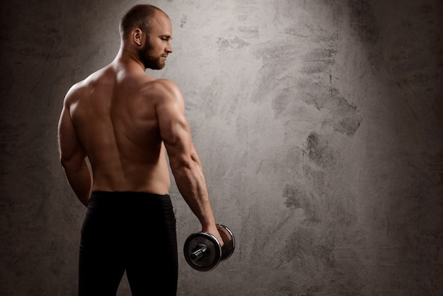 Young powerful sportsman training with dumbbells over dark wall.