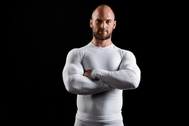 Young powerful sportsman in white clothing over black wall.