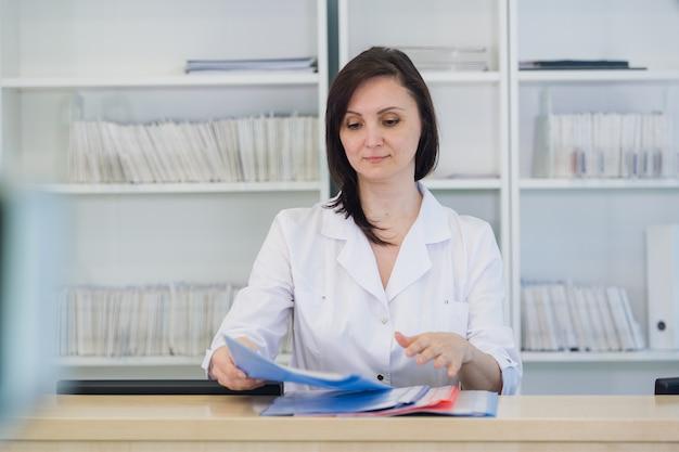 클리닉 리셉션 데스크에서 일하는 젊은 개업 의사