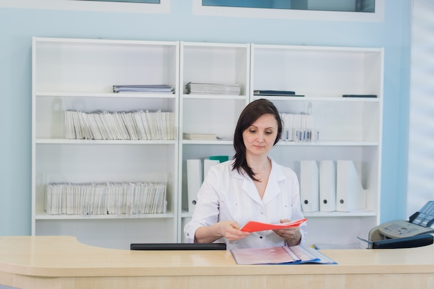 Young practitioner doctor working at the clinic reception desk, she is answering phone calls and scheduling appointments