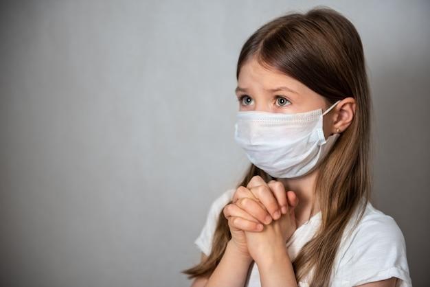 보호 마스크를 쓰고기도하는 어린 소녀