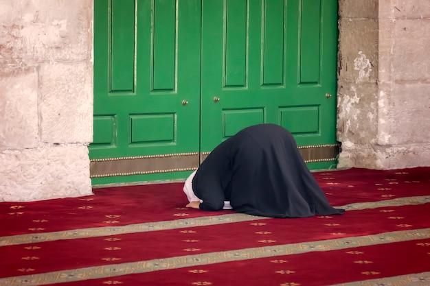 イスラエルのエルサレムの旧市街のイスラム教徒地区にあるモスクの岩のドームにひざまずいて祈る若い女性。