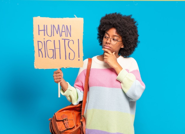 Young pre afro woman protesting with human rights banner