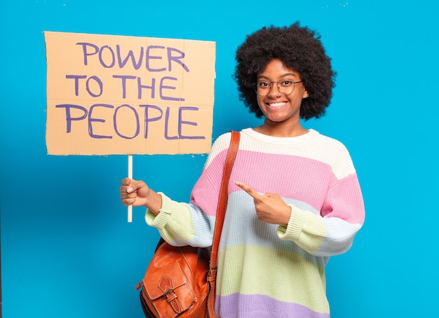 Young pre afro woman protesting with  a power to the people banner