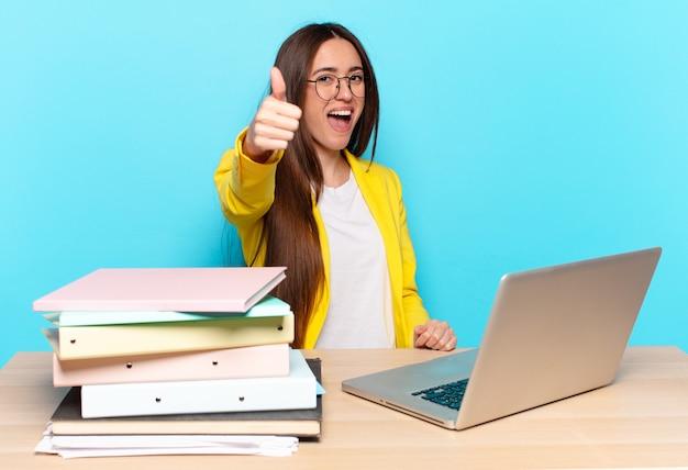 Молодая предпринимательница чувствует себя гордой, беззаботной, уверенной и счастливой, позитивно улыбается, показывает палец вверх