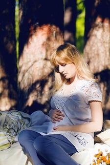 Молодая беременная белокурая женщина спит в кровати в природе. концепция хорошего сна