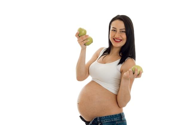 Молодая беременная брюнетка женщина позирует с зелеными яблоками, изолированными на белой стене