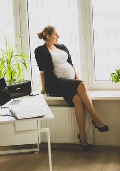 Молодая беременная бизнесвумен сидит на подоконнике и разговаривает по телефону