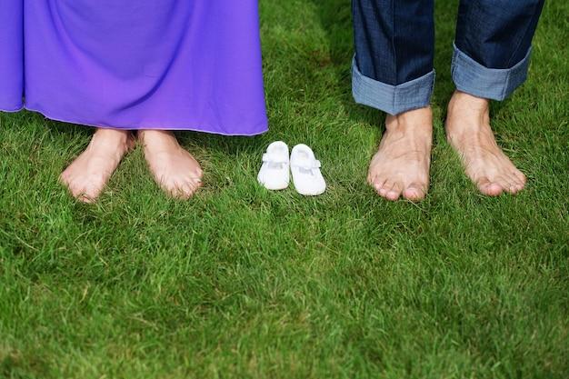 生まれたばかりの赤ちゃんのブーティと緑の芝生に裸足で若い妊娠中のカップルの足