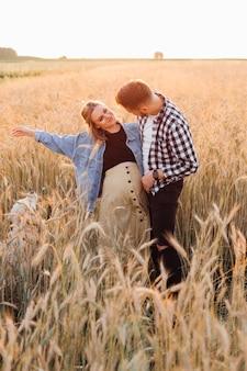 Молодые беременные пары имеют столько счастья и любви, что летним вечером им хочется охватить весь мир беременности и заботы. в ожидании новой жизни. забота и внимание. любовь и внимание.