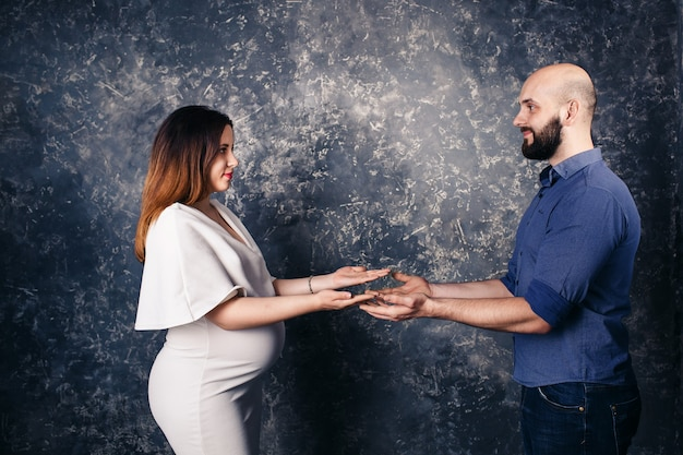 손바닥에 copyspace 들고 젊은 임신 부부.