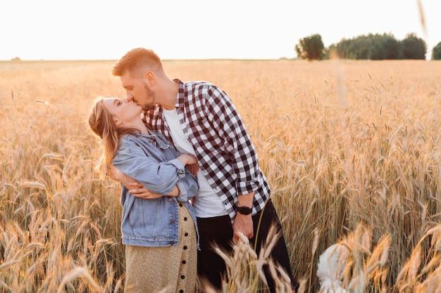 젊은 임신한 부부는 여름 저녁에 저녁 산책을 하는 동안 들판에서 키스를 하고 있습니다. 임신과 보살핌. 행복과 부드러움. 배려와 관심. 사랑과 희망 .가족 가치. 건강한 생활 방식.