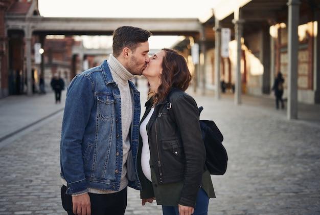 길거리에서 키스하는 젊은 임신 부부