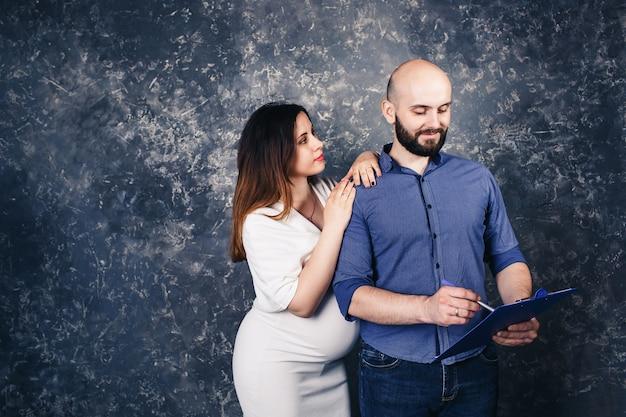 그들의 손에 클립 보드와 젊은 임신 부부.