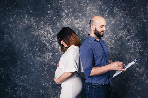 手にクリップボードを持つ若い妊娠中のカップル