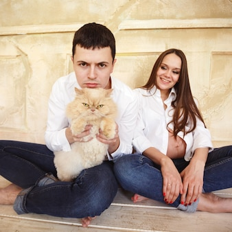 Young pregnant couple with cat