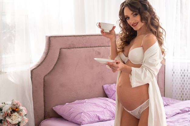 Young pregnant girl drinks coffee in bed