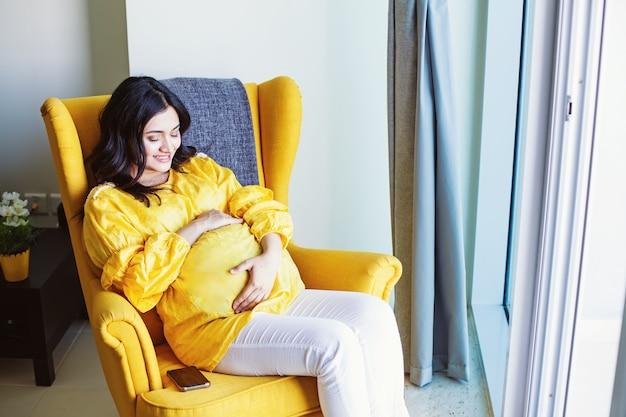 自宅の肘掛け椅子に座っている若い妊娠中のインドの女性