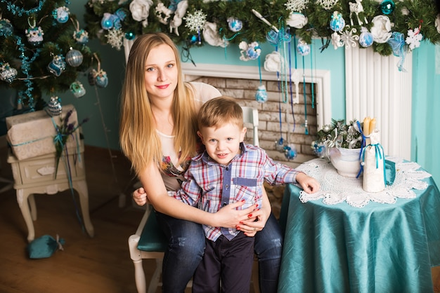 Young pregnant mother and child celebrating christmas at home