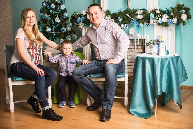 Young pregnant mother, father and their child celebrating christmas at home
