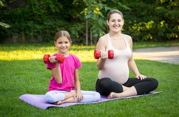 公園で芝生の上でヨガを練習している若い妊娠中の母親