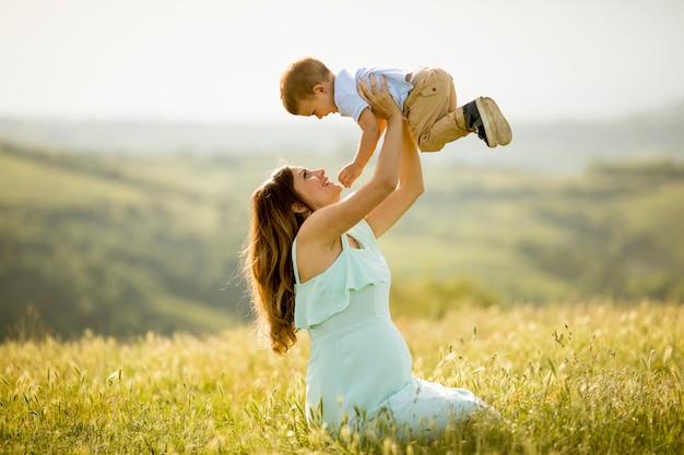 아름 다운 화창한 날에 필드에 그녀의 귀여운 작은 소년과 젊은 임신 어머니
