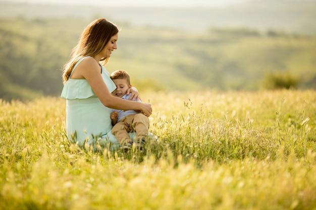 美しい晴れた日にフィールドに彼女のかわいい男の子と若い妊娠中の母親