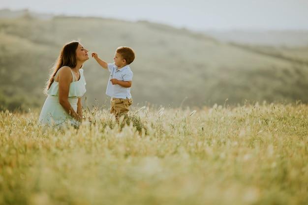 美しい晴れた日にフィールドで彼女のかわいい男の子と若い妊娠中の母親