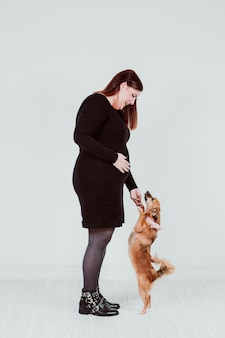 Young pregnant woman of 21 weeks at home with her cute small dog. family concept