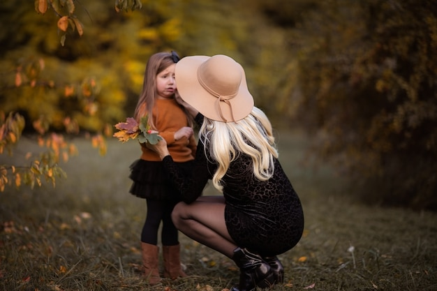 Young pregnant woman in autumn hat feeling sorry to her little daughter in the park