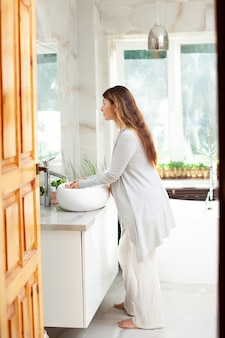 A young pregnant woman in a bright bathroom washes her arms. morning routine. self-care. hygiene. home wear. high quality photo