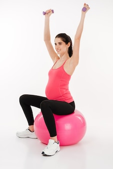Young pregnant woman doing exercise using fitness ball and dumbbells