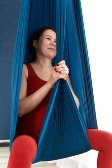 Young pregnant woman doing exercises of aerial yoga in hammock.