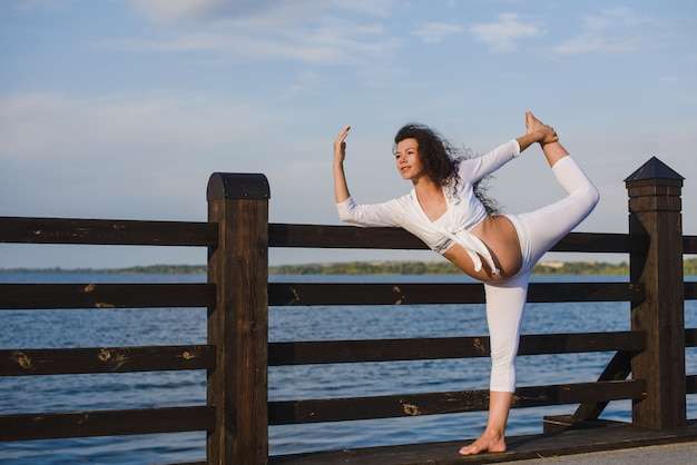 Young pregnant woman doing yoga by the river