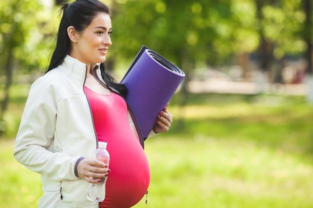 Молодая беременная женщина делает упражнения йоги на открытом воздухе в парке.