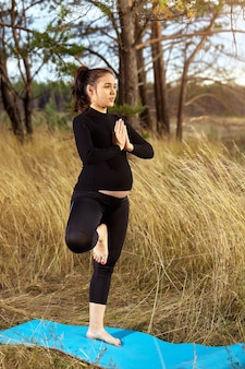 Молодая беременная женщина занимается йогой на природе