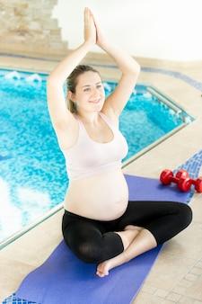 スイミングプールの横にあるフィットネスマットでヨガをしている若い妊婦