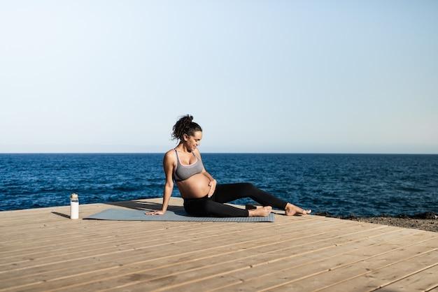 屋外でヨガをしている若い妊婦