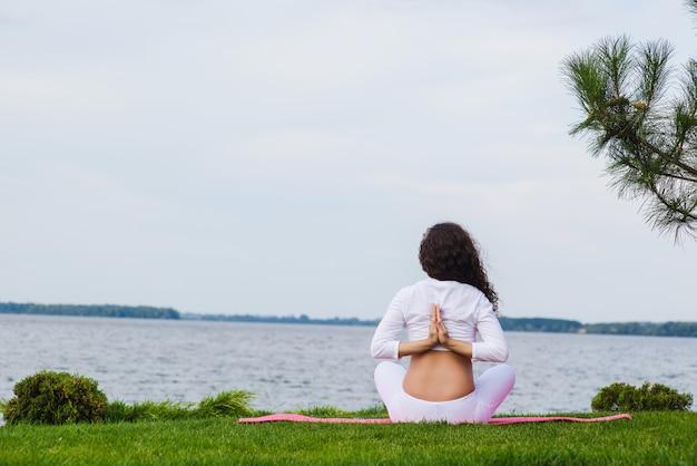 屋外ヨガをやっている若い妊娠中の女性