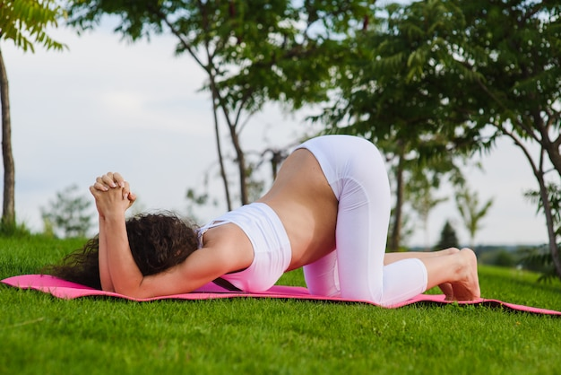 Young pregnant woman doing yoga outdoors