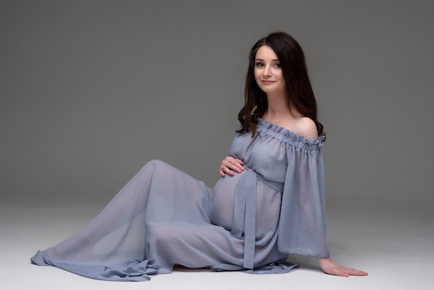 A young pregnant woman in a dress is sitting on the floor in the studio.