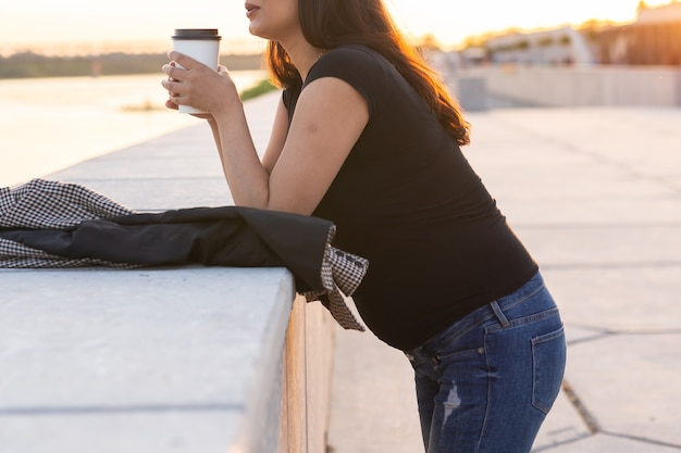 Молодая беременная женщина пьет кофе или чай на вынос на набережной. концепция материнства, отдыха и здоровья.