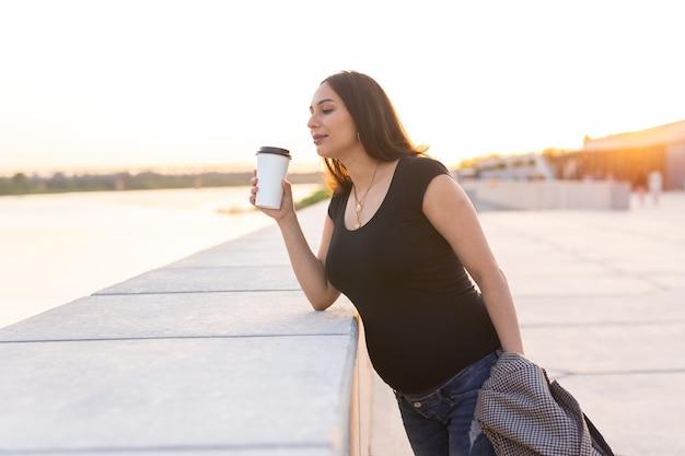 Молодая беременная женщина пьет кофе или чай на вынос на набережной для отдыха и здоровья по беременности и родам