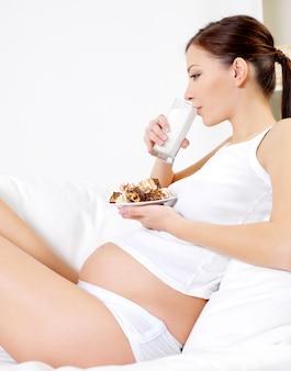 Молодая беременная женщина пьет молоко с тортом, сидя дома
